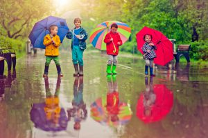 Little boys and girl happily walking under umbrella in park
